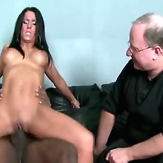Busty brunette MILF mounts black thug as her man watches her